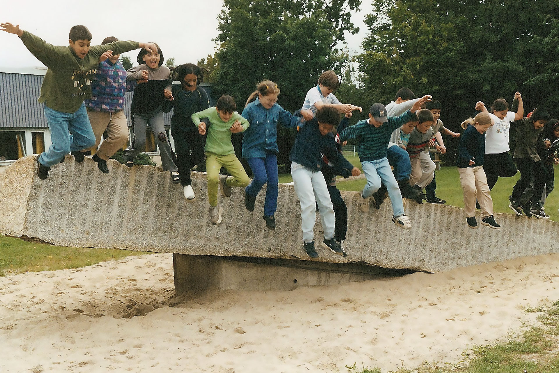 Klasse springt von einem grossen Stein auf dem Schulareal