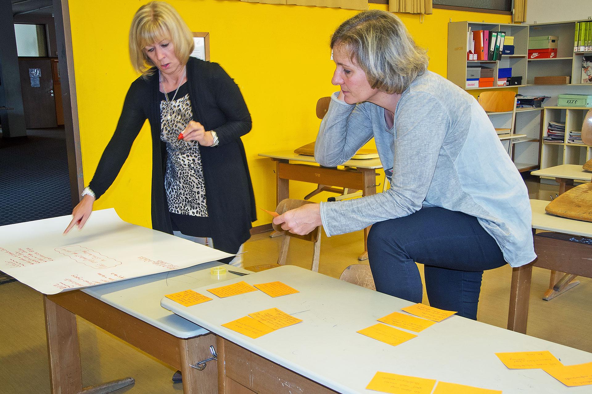 zwei Lehrerinnen erstellen ein Plakat mit Ergebnissen aus einer Besprechung