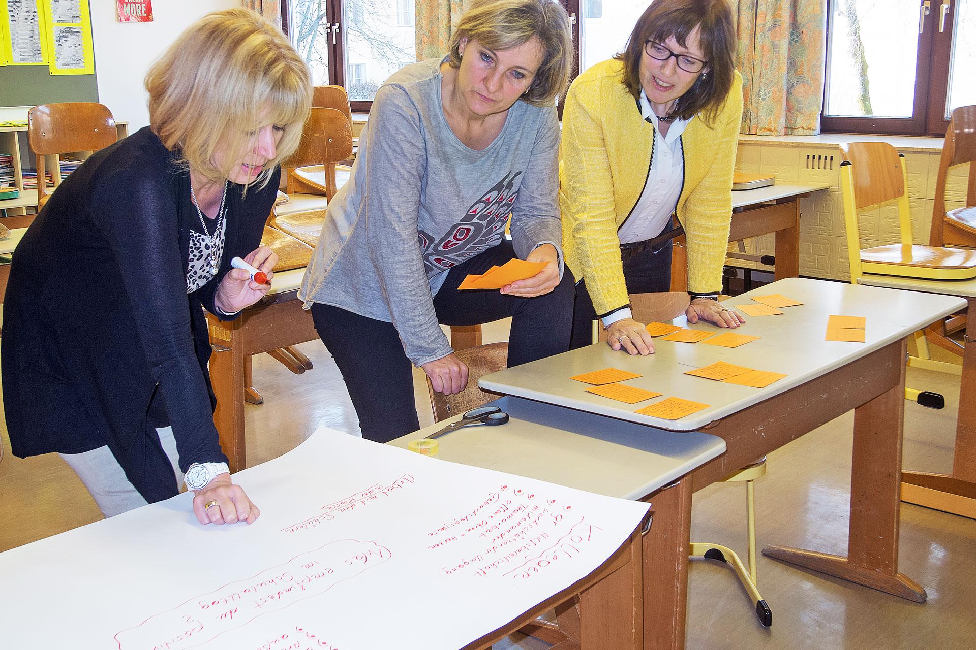 drei Lehrerinnen erstellen ein Plakat mit Ergebnissen aus einer Besprechung