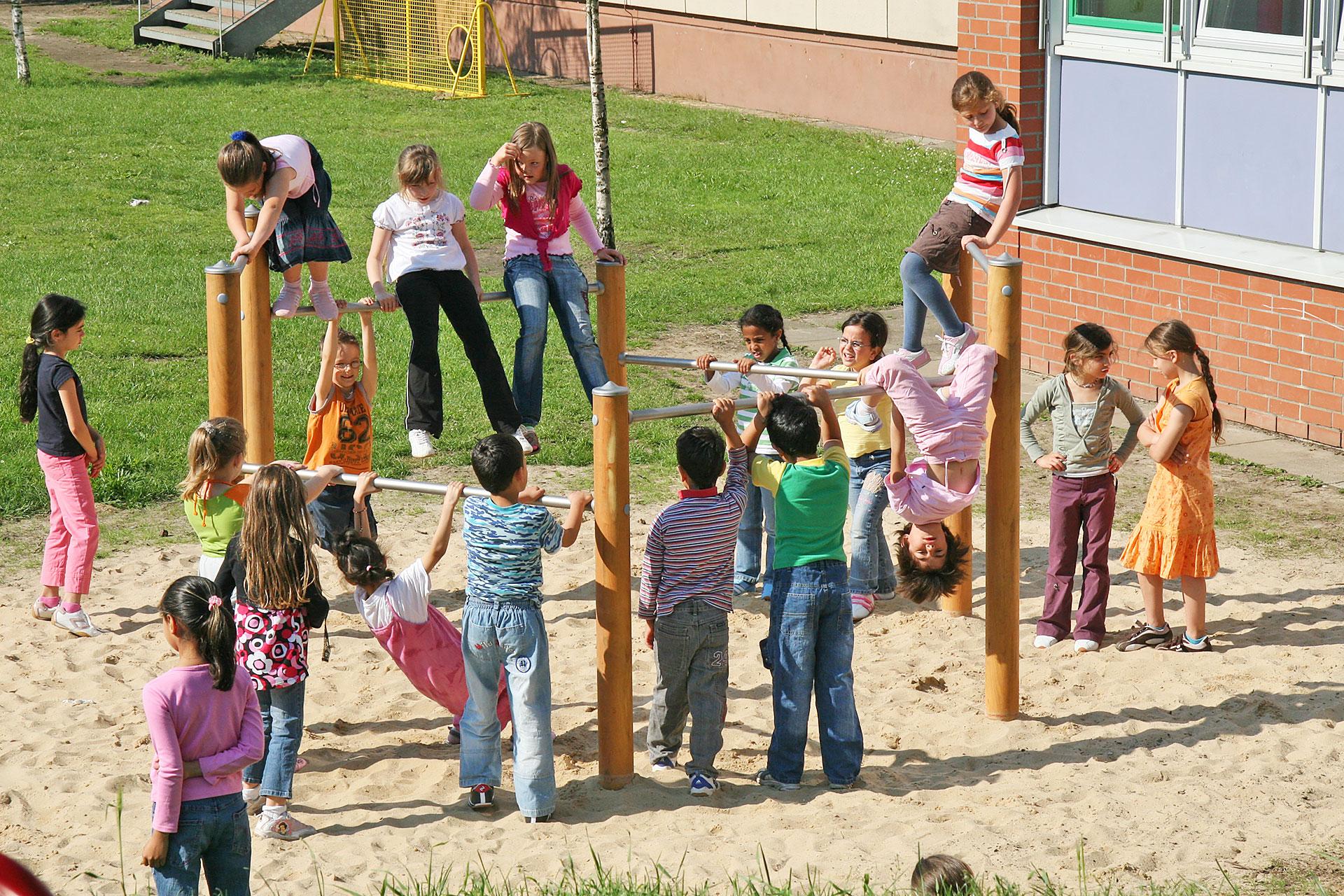 Schüler/innen turnen auf den Reckstangen auf dem Schulareal