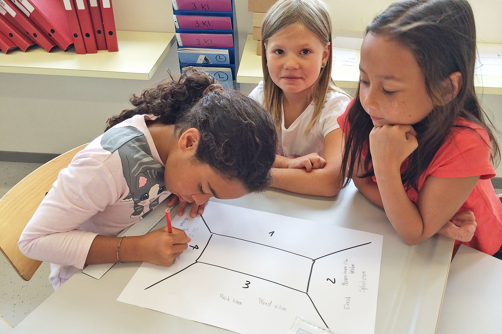 drei junge Schülerinnen füllen ein Placemat aus