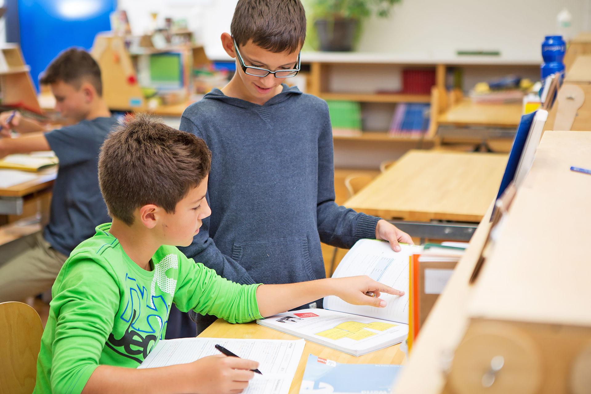 zwei Schüler besprechen Aufgaben an einem persönlichen Arbeitsplatz in einer Lernlandschaft