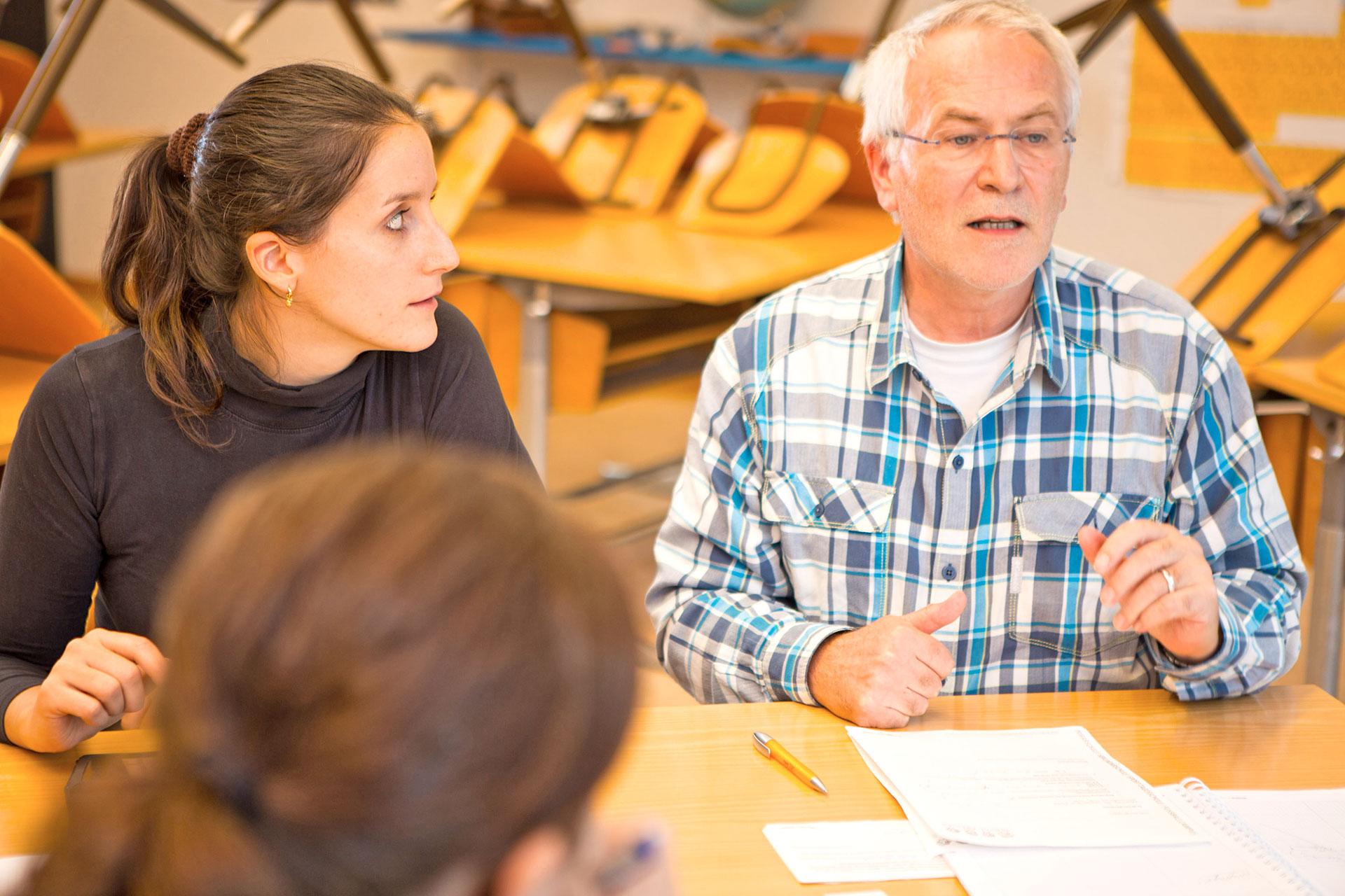 zwei Personen während einer Besprechung in einem Schulzimmer