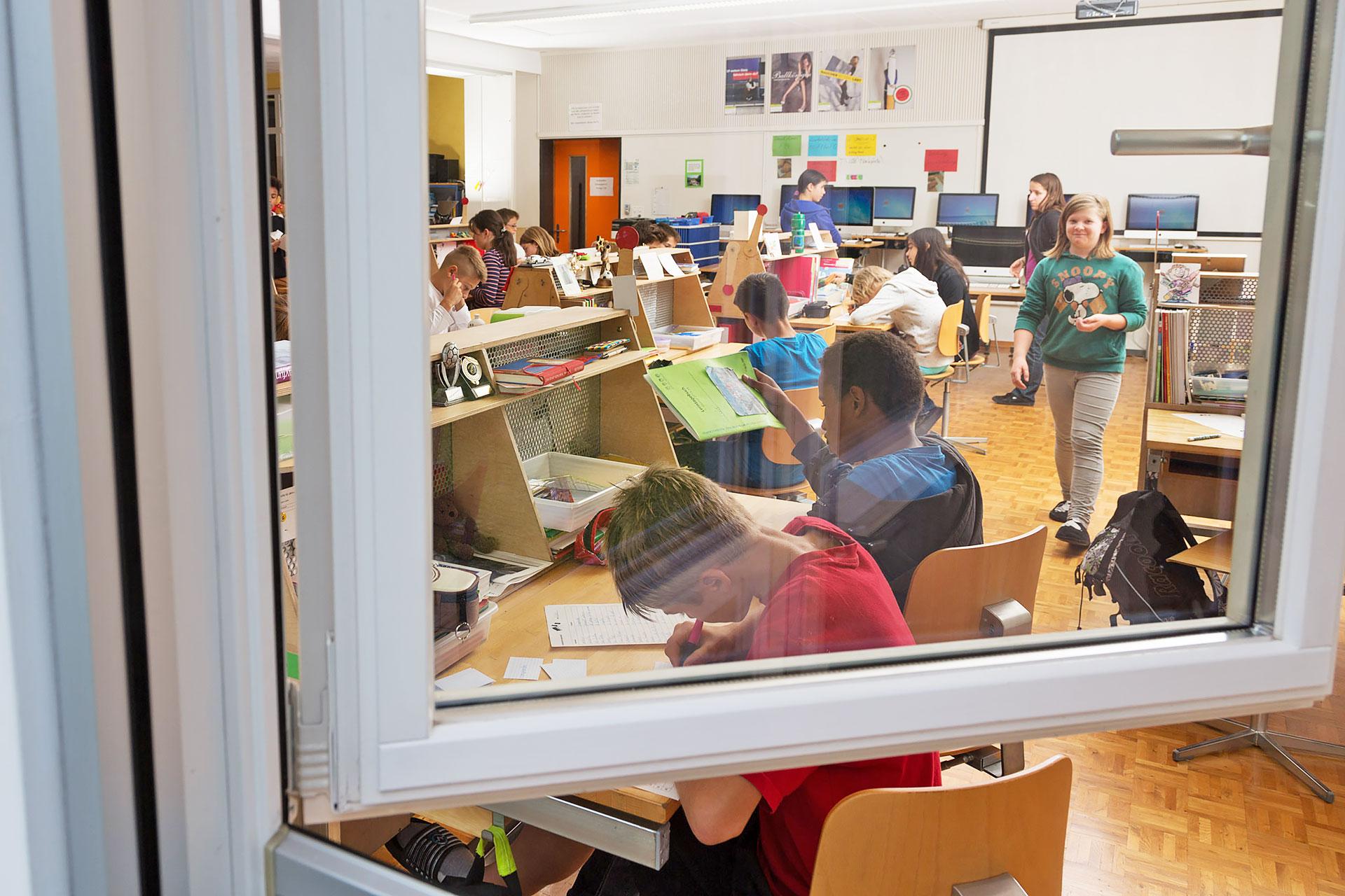 Blick durch ein Fenster in ein Schulzimemr mit persönlichen Arbeitsplätzen für Schüler/innen