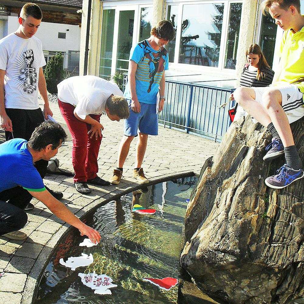 eine Klasse führt Wasserexperimente im Schulbrunnen durch