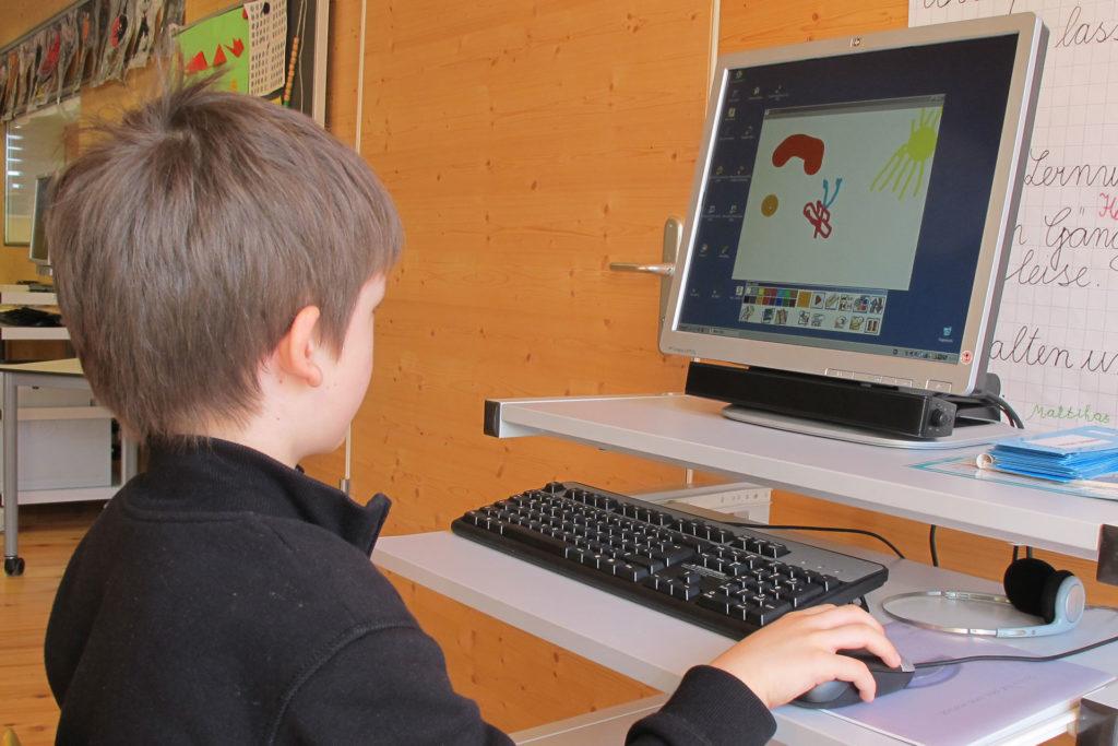 ein Schüler malt am Computer