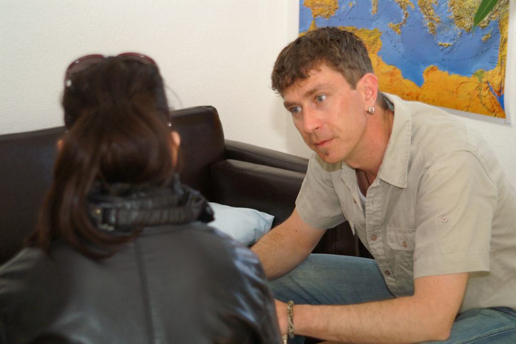 Lehrer im Gespräch mit einer Schülerin