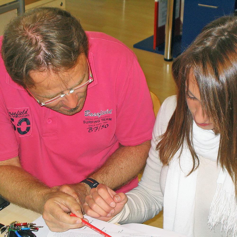 Lehrer erklärt einer Schülerin eine Aufgabe