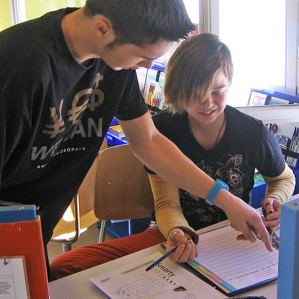 eine Schülerin füllt zusammen mit einem Mitschüler ein Arbeitsblatt aus