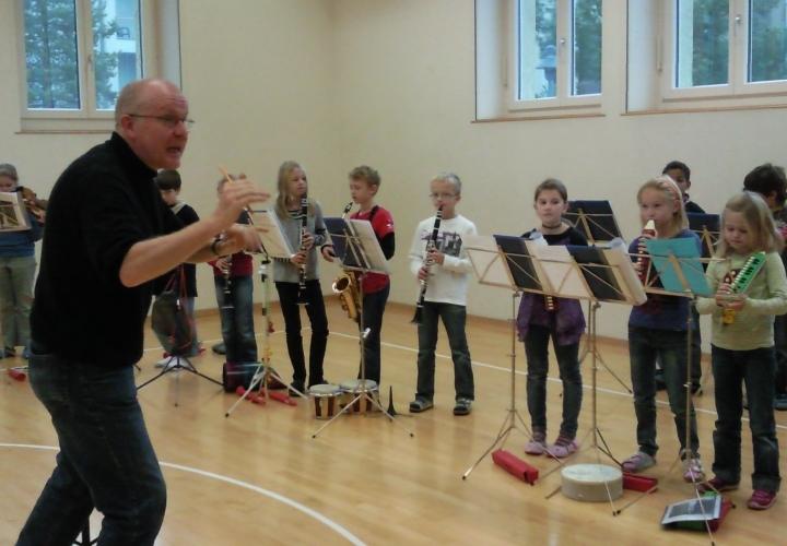 Schüler spielen im Orchester mit Klarinette / Saxophon und Triola