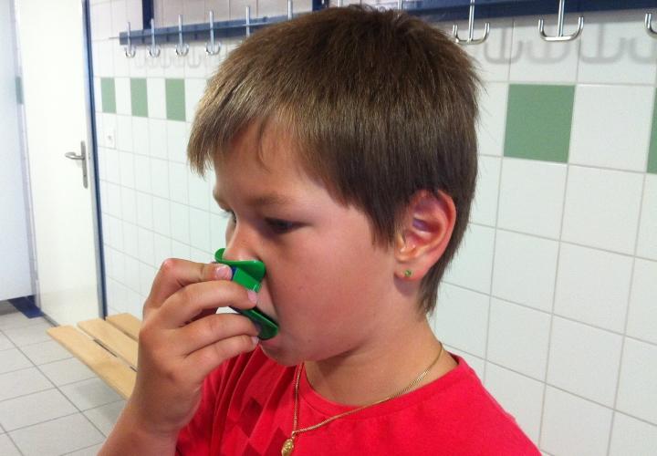 Schüler übt mit der Nasenflöte in einer Garderobe