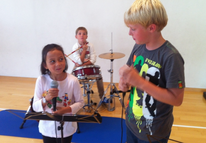drei Schüler/innen üben einen Rap mit Schlagzeug ein