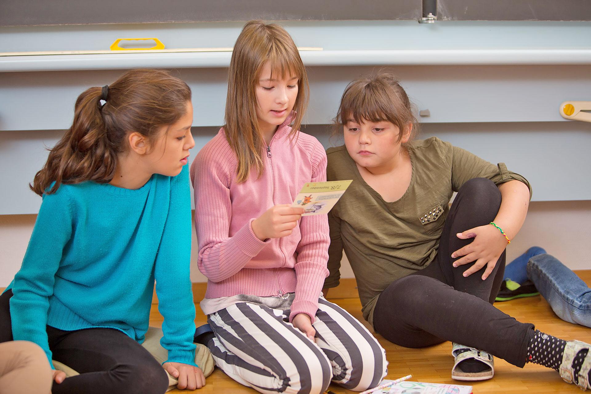 drei Schülerinnen sitzen auf dem Schulzimmerboden und lesen eine Aufgabenkarte