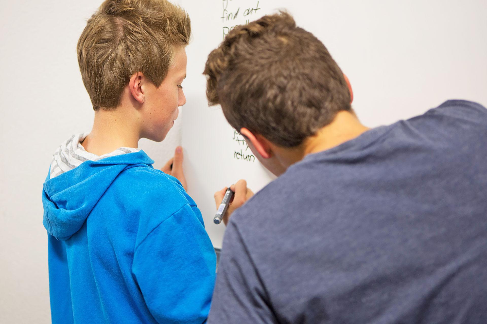 zwei Schüler arbeiten kooperativ an einer Aufgabe am Whiteboard