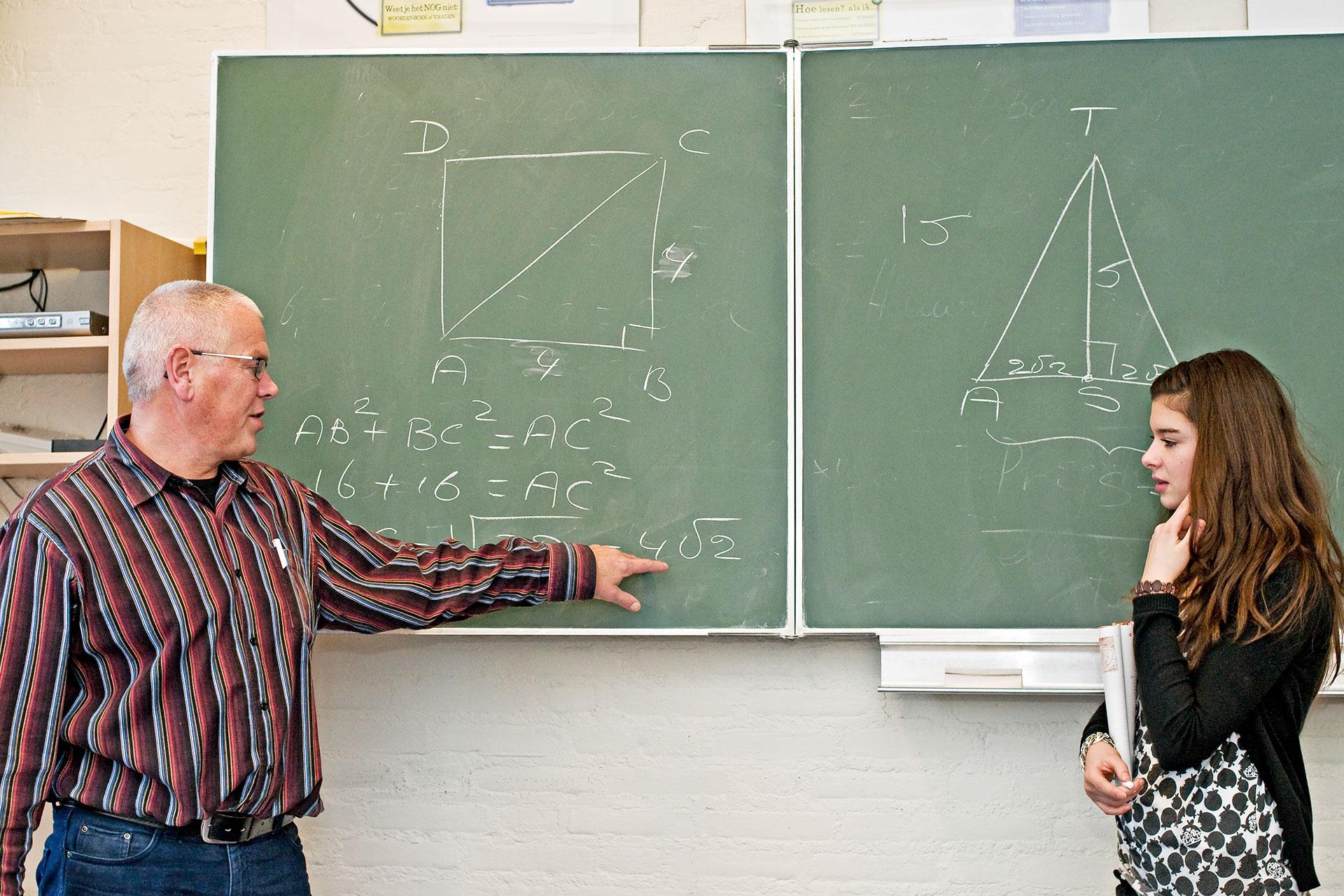 Lehrer gibt an der Wandtafel direkte Instruktion