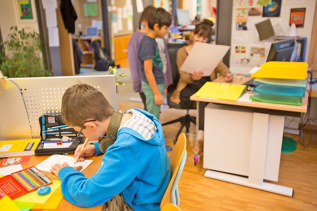 ein Schüler sitzt an seinem persönlichen Arbeitsplatz