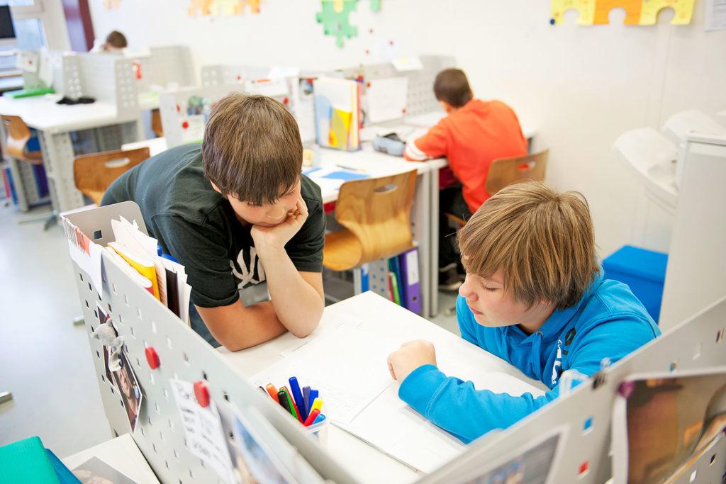 zwei Schüler arbeiten kooperativ an einer Aufgabe an einem persönlichen Arbeitsplatz im Schulzimmer