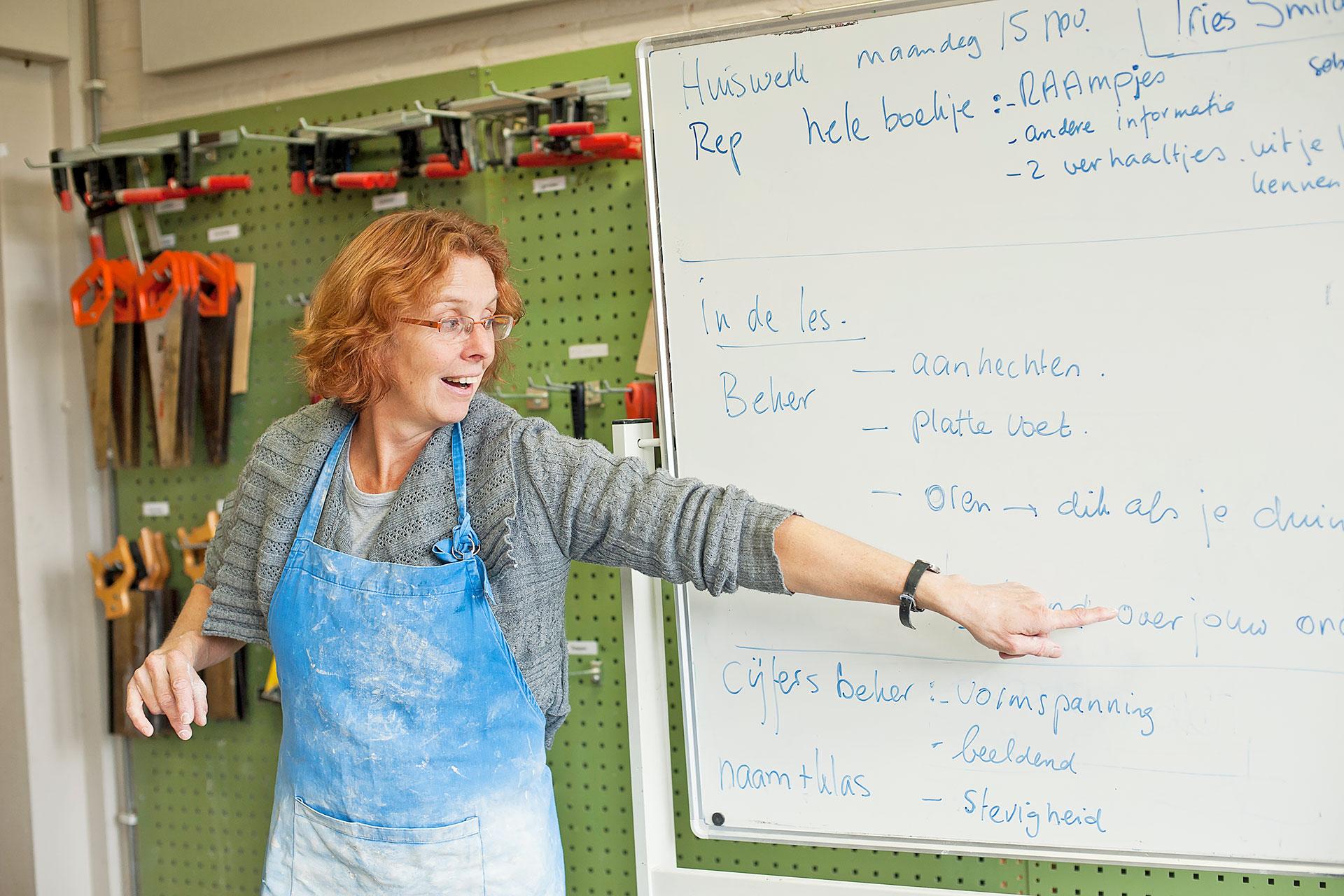 Lehrerin im Werkraum erläutert eine Aufgabe
