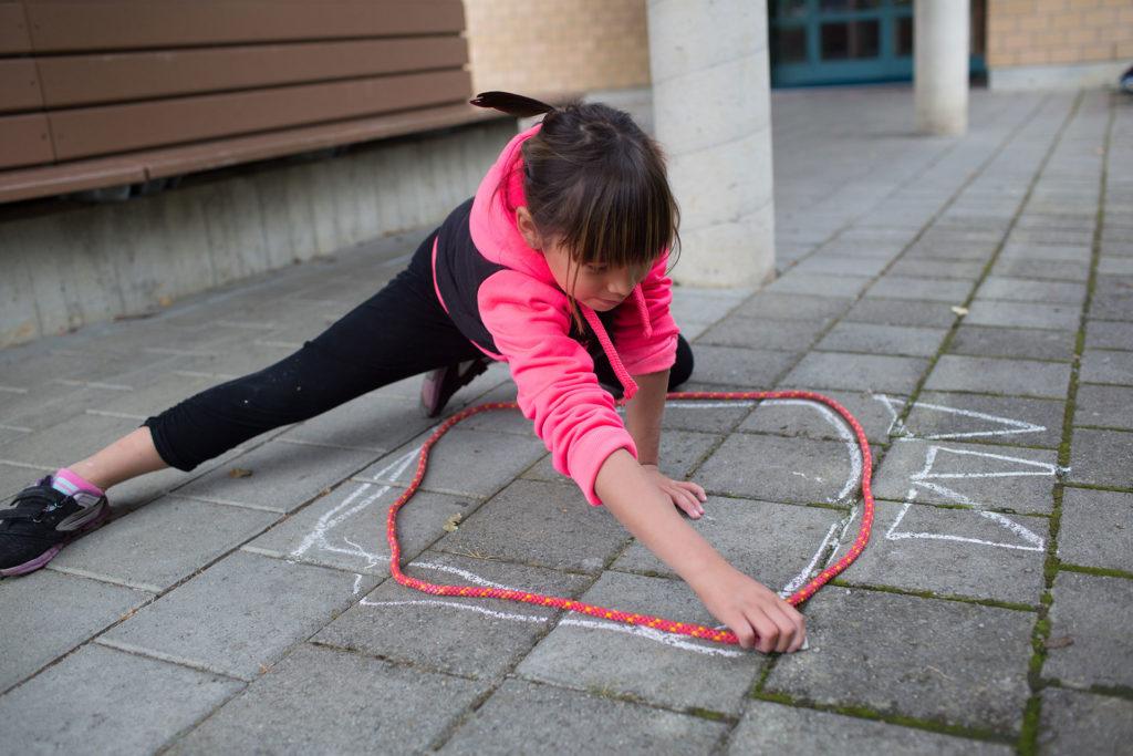 Schülerin zeichnet eine Kreidekreis entlang einer Schnur auf den Schulplatzboden