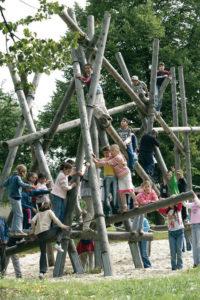 Schüler/innen klettern im Stangengestrüpp auf dem Schulareal herum