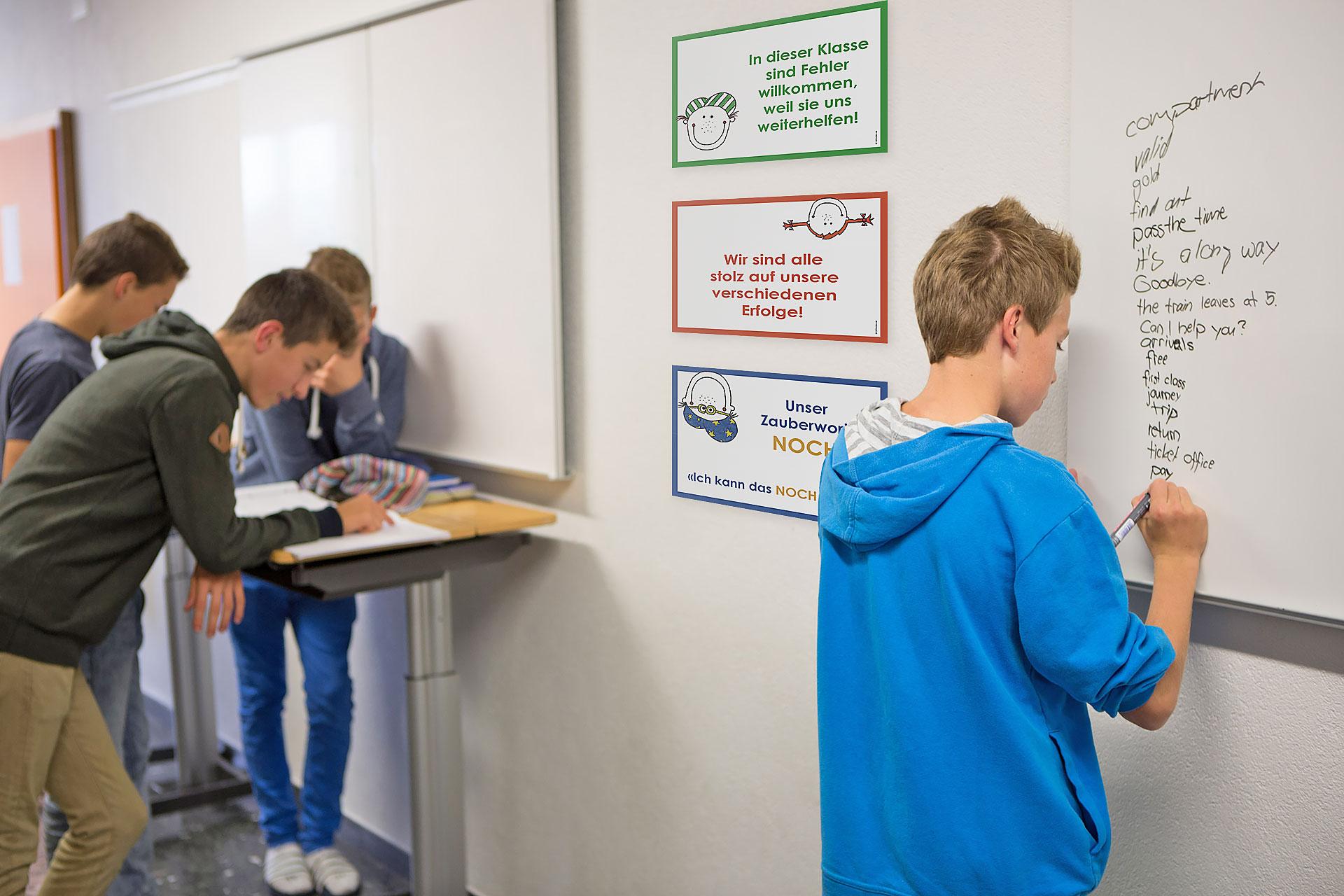 Schüler arbeitet am Whiteboard neben den Kleinplakaten Mindset