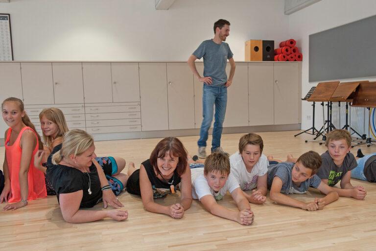 Lehrerinnen und Schüler/innen während einer Bewegungsübung