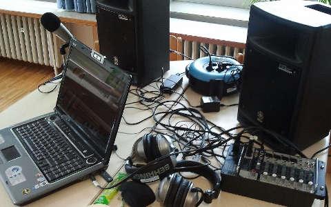 Laptop mit angeschlossenem Mikrofon, Kopfhörer, Lautsprecher auf einem Tisch