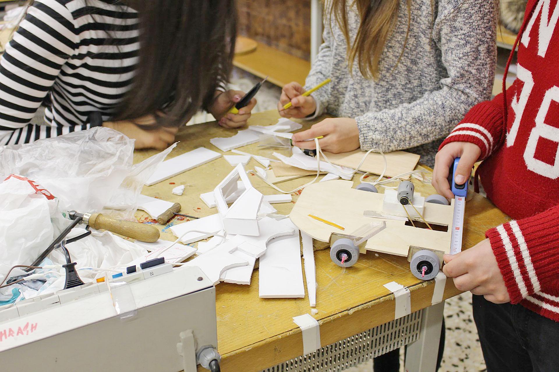 Schülerinnen bauen ein Fahrzeug im Werkunterricht