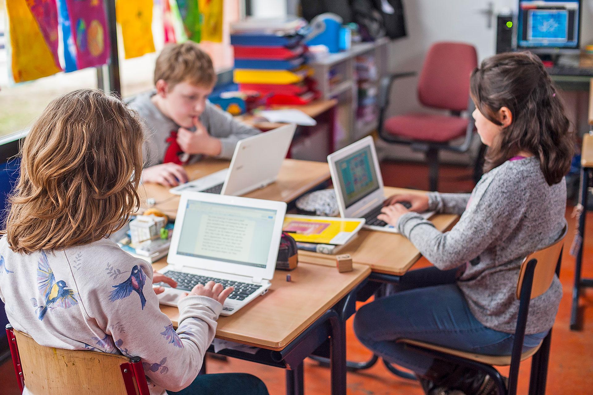 Schüler/innen arbeiten an Laptops im Schulzimmer