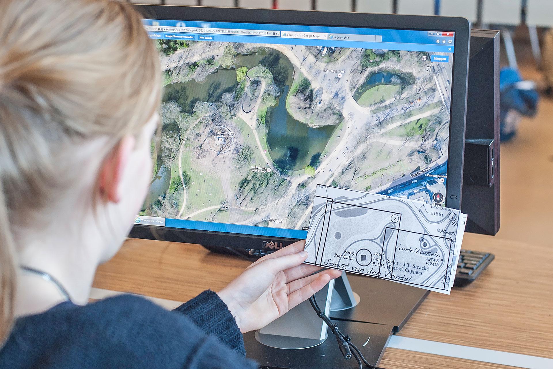 Schülerin vergleicht einen Kartenausschnit mit Google Maps auf dem PC