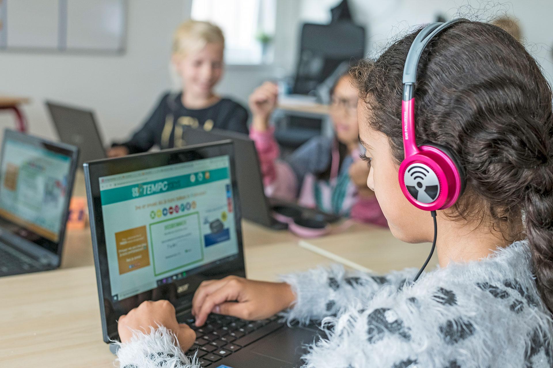 Schülerin mit einem Laptop und Kopfhörern in der Schule