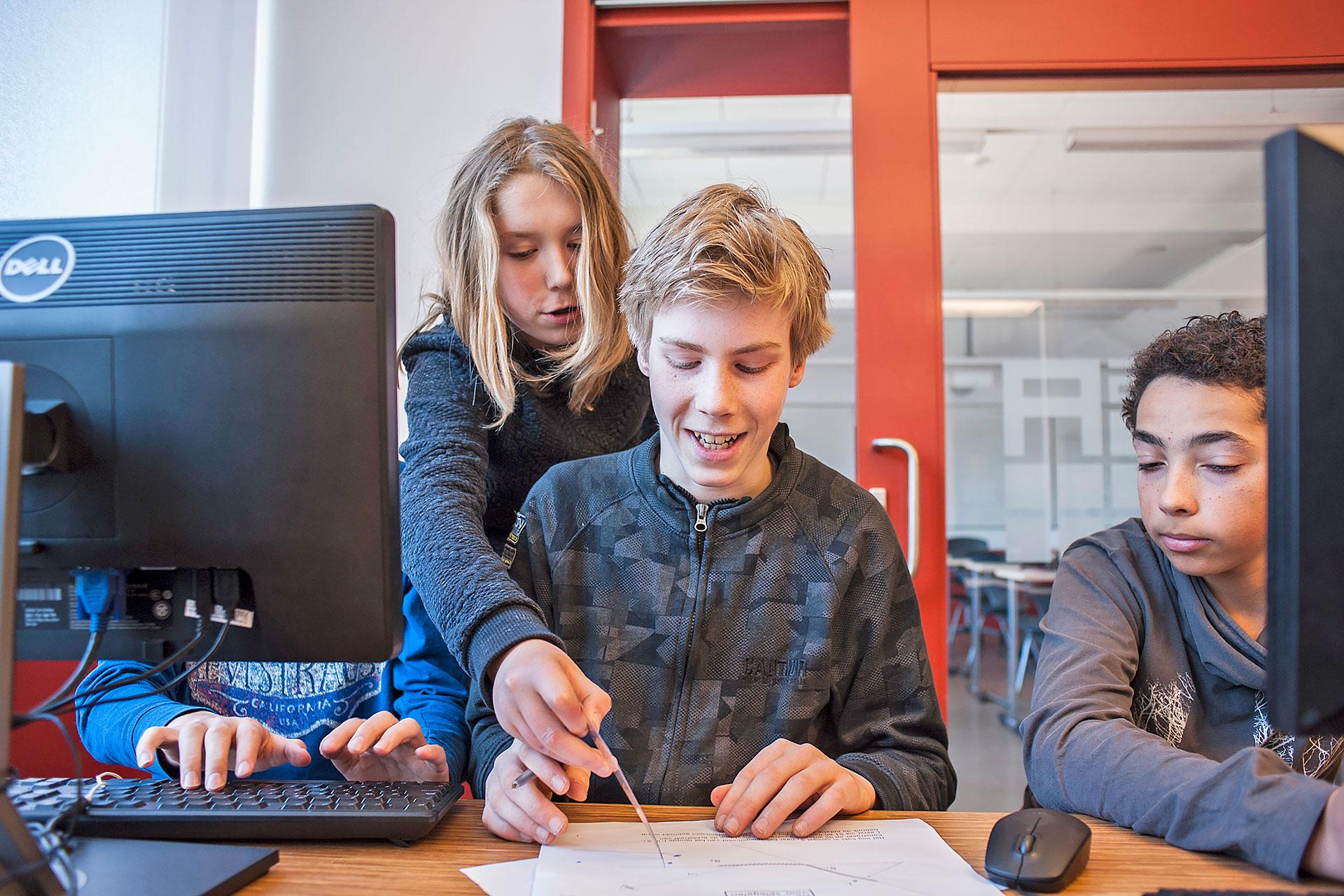 Schüler/innen lösen Aufgaben auf dem Arbeitsblatt mit Hilfe von Computern