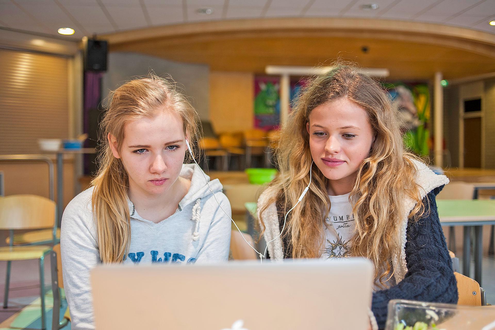zwei Schülerinnen sitzen vor einem Laptop und teilen die Kopfhörer