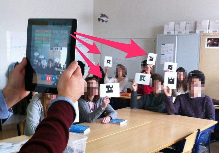 Lehrer fotografiert mit dem Tablet die Antworten der Klasse mit Plickers-Karten