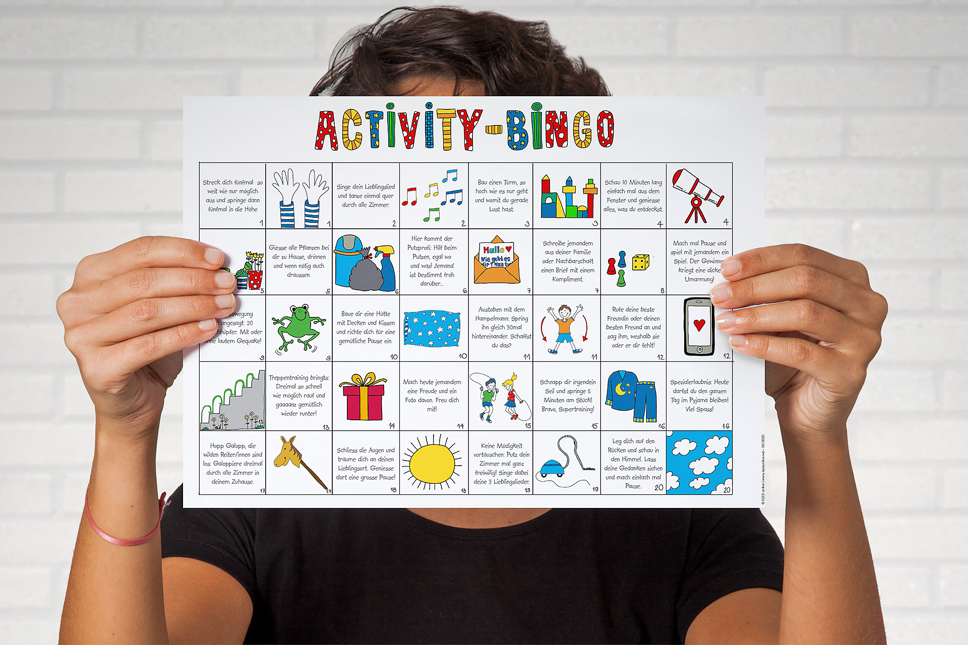 Person hält ein Blatt mit dem Activity-Bingo in die Kamera