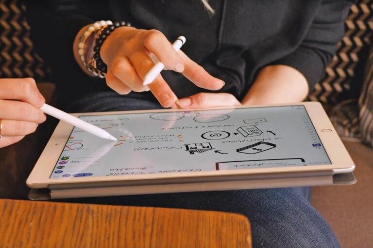 zwei Schülerinnen arbeiten an einem Tablet mit Explain Everything