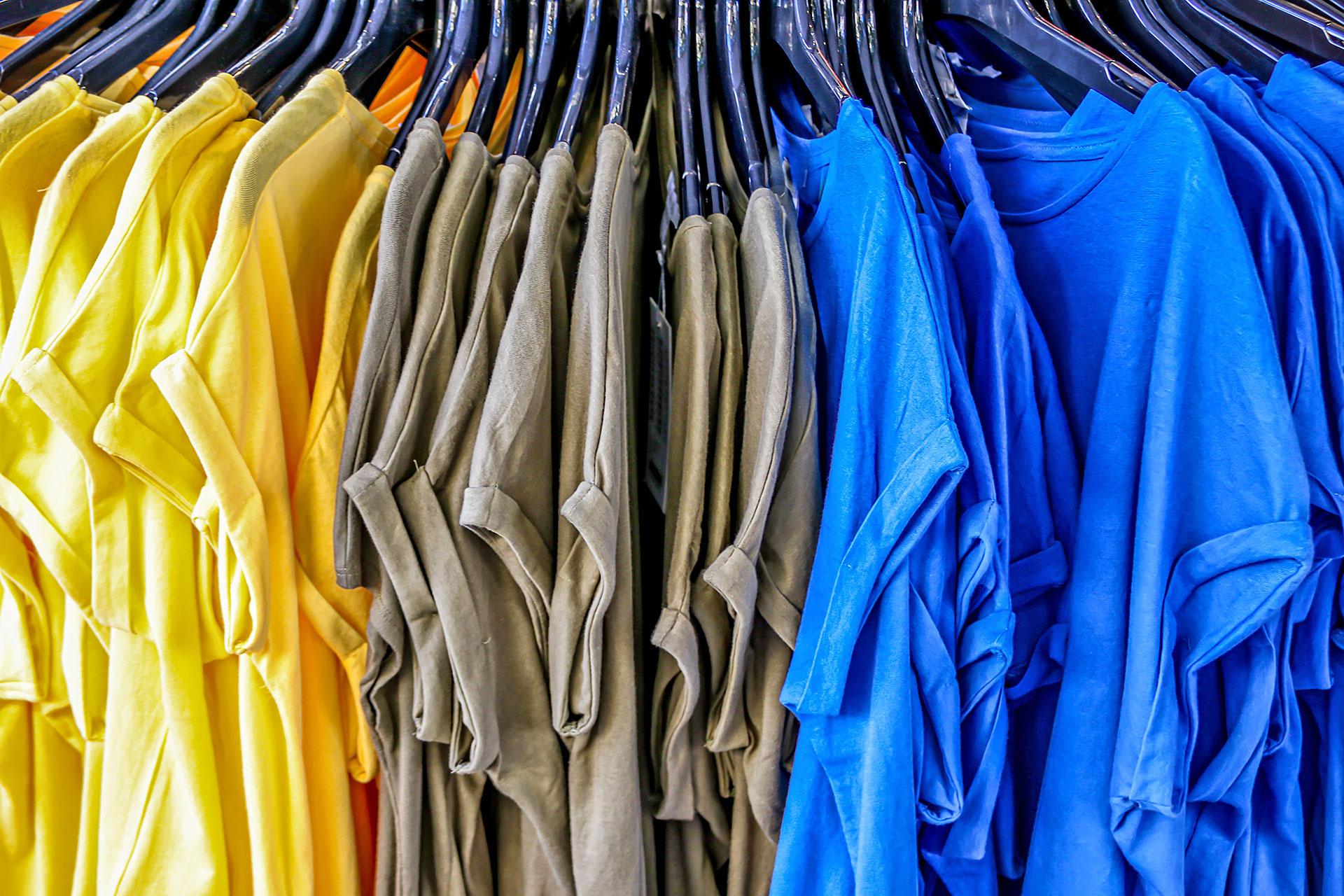 farbige T-Shirts hängen an Bügeln