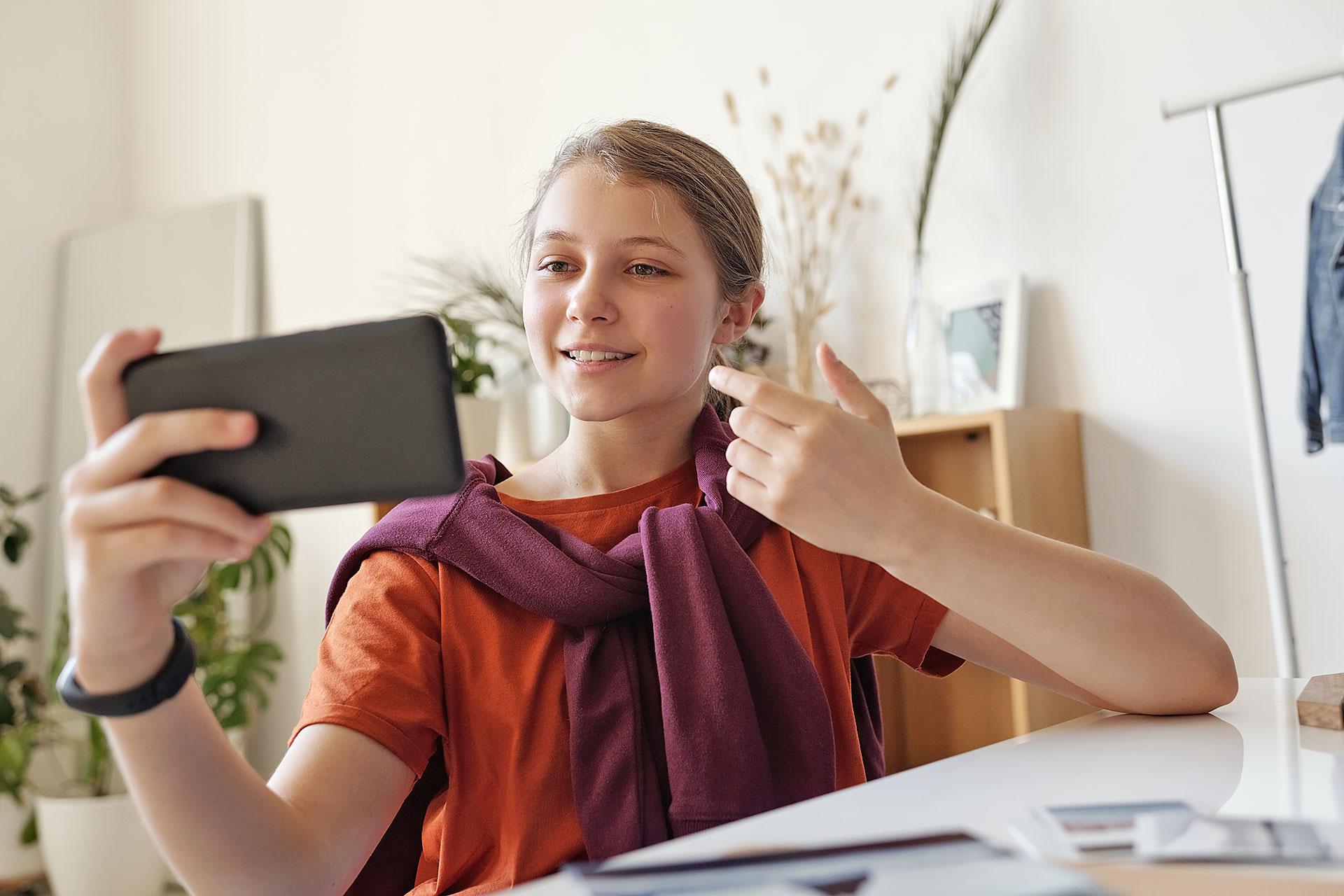 Schülerin chatet mit dem Smartphone