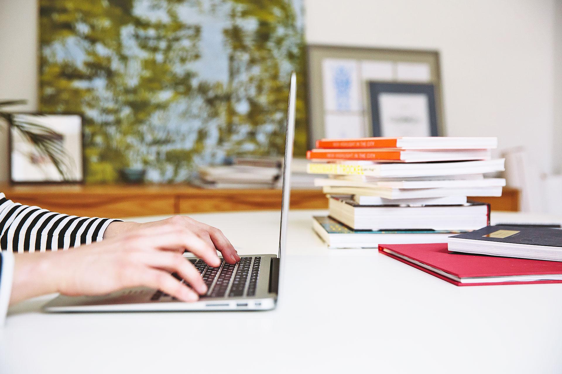 Person arbeitet am Laptop im Wohnzimmer