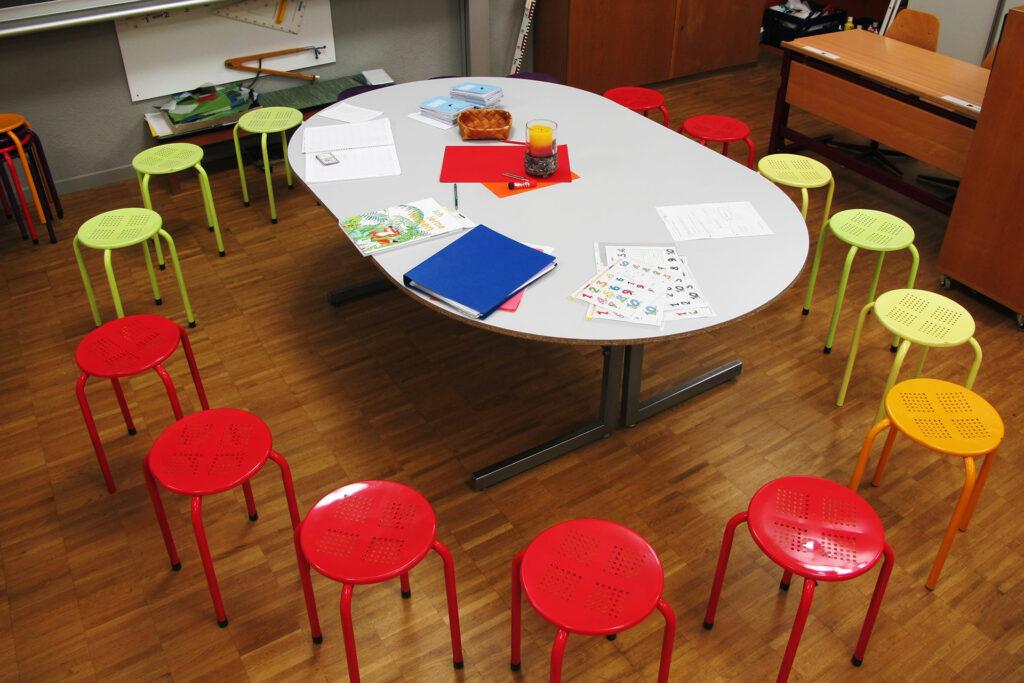 Stuhlkreis um einen Tisch im Schulzimmer