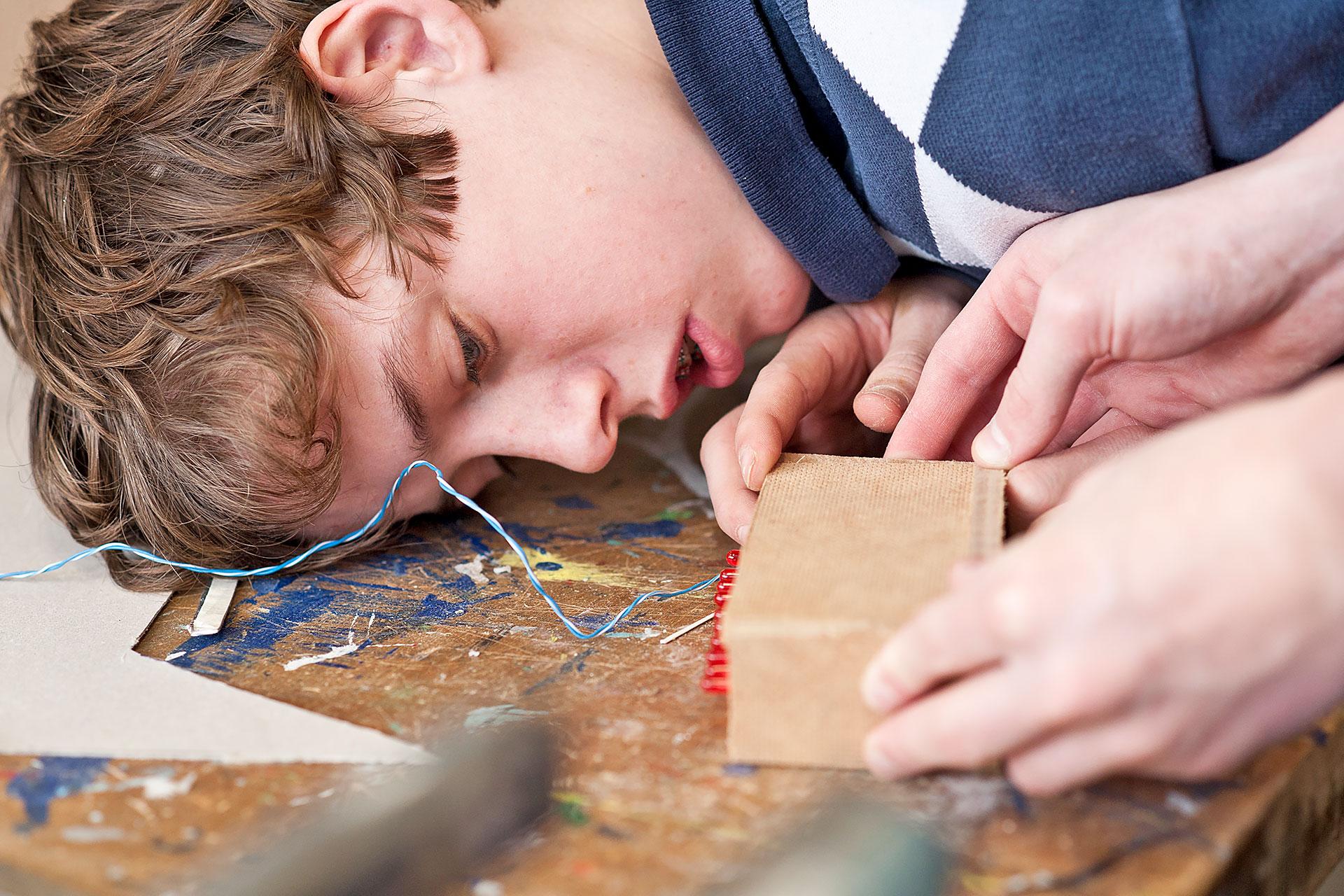 Junge lehnt sich über ein Kästchen mit LED-Dioden