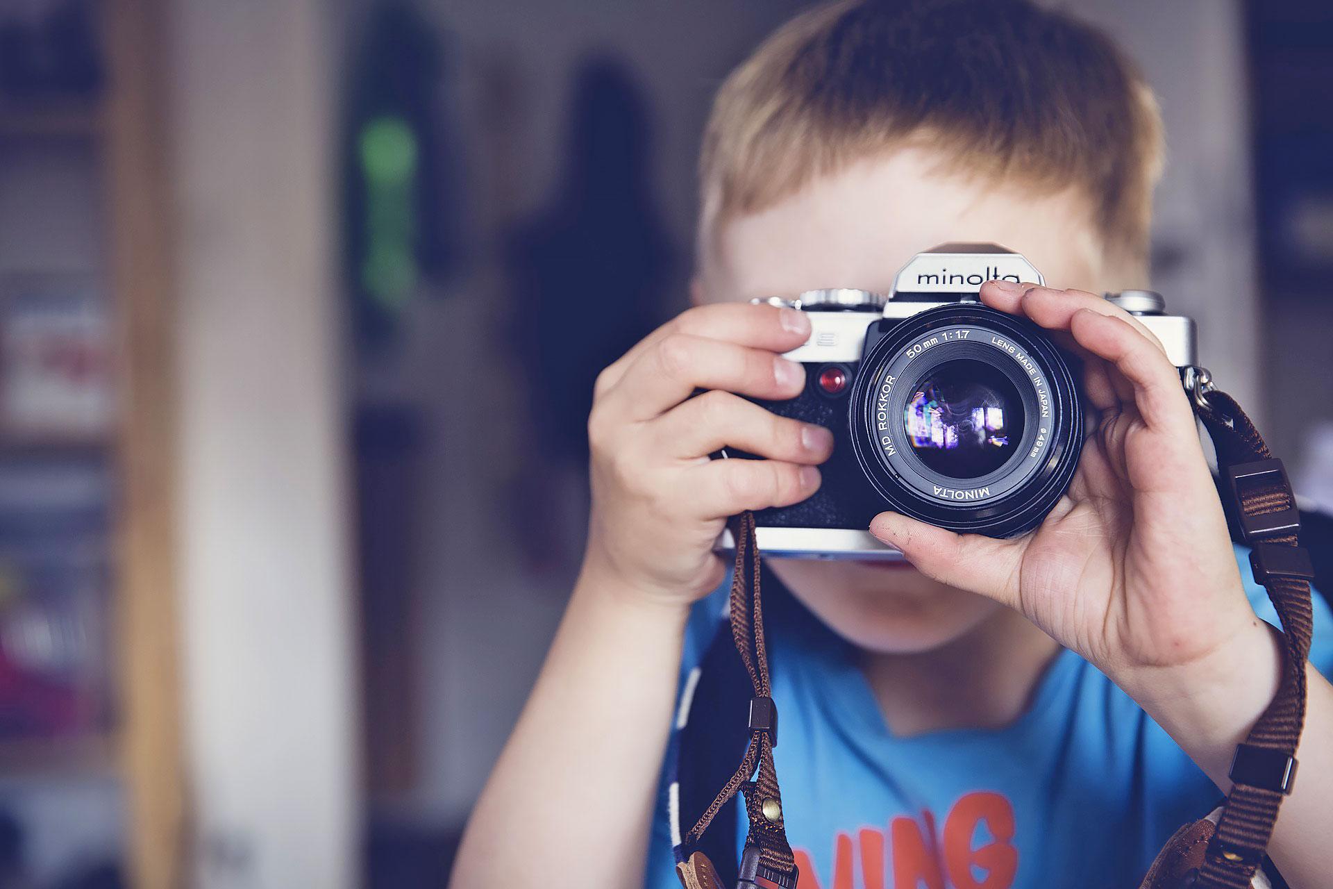 kleiner Junge mit einer Minolta-Fotokamera