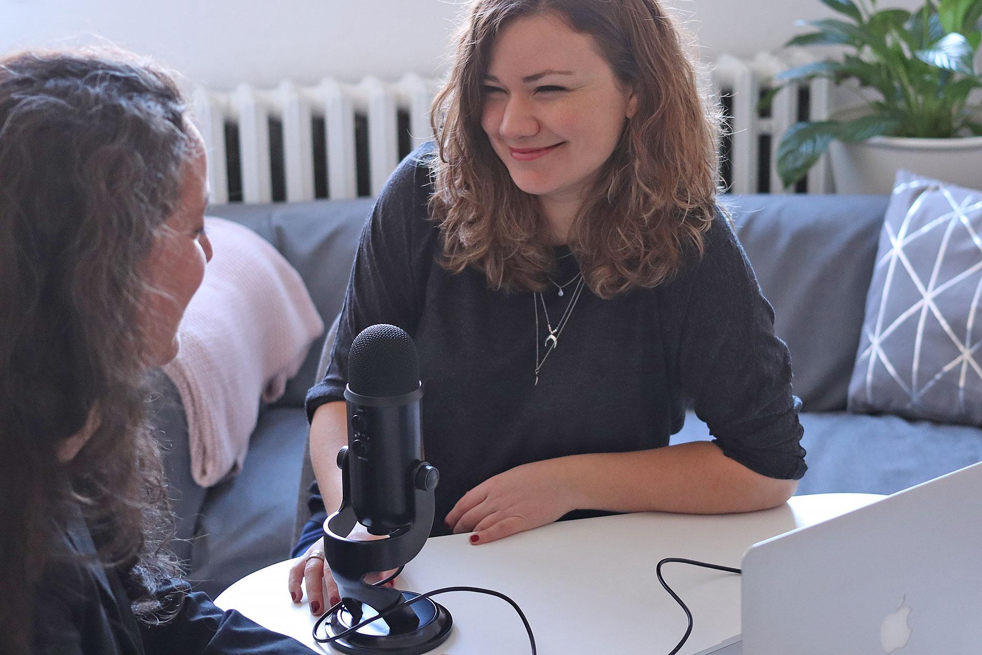 zwei junge Frauen mit einem Mikrofon nehmen im Wohnzimmer einen Podcast auf