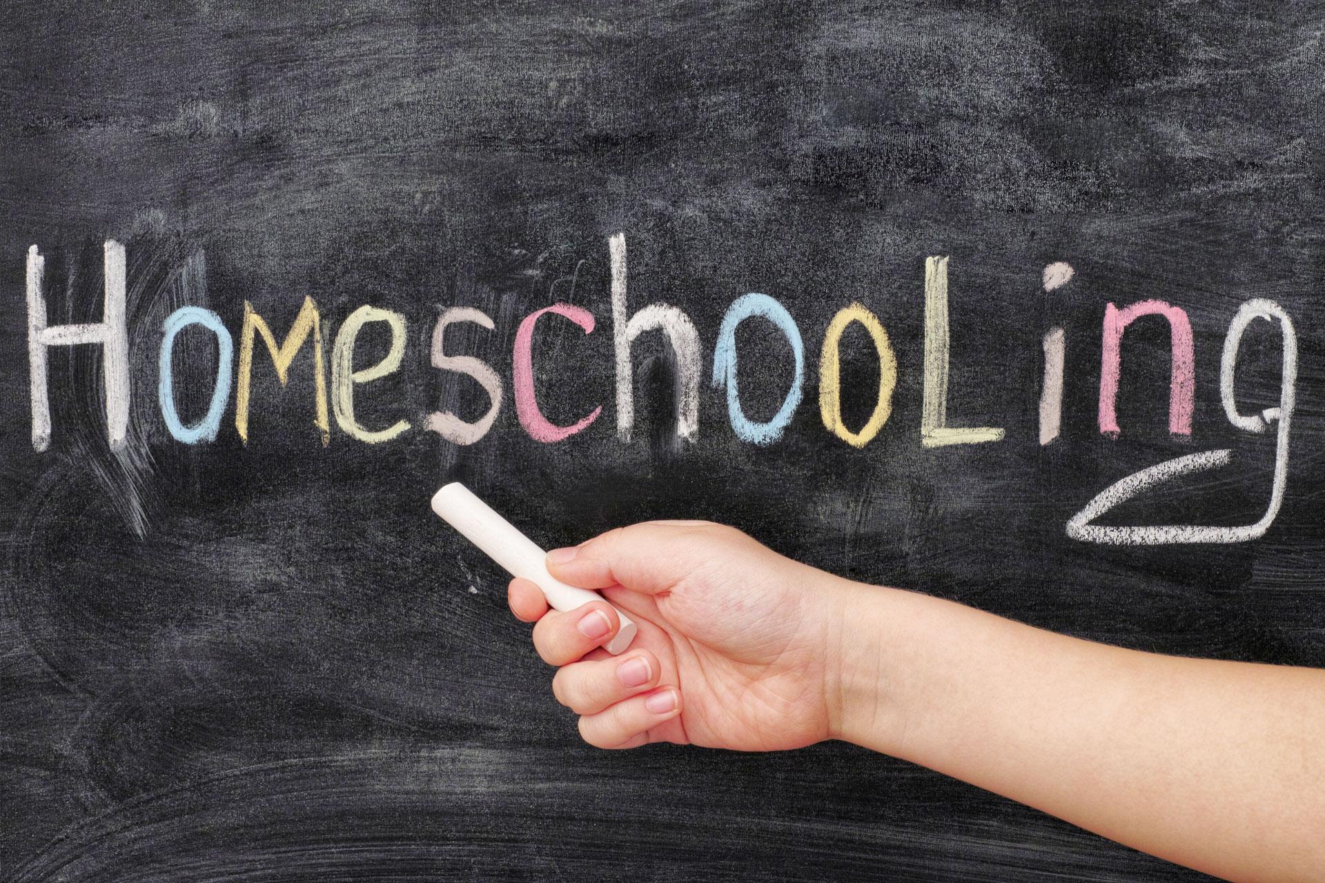 """Hand, die eine Kreide hält, vor einer Wandtafel mit Kreideschriftzug """"Homeschooling"""""""