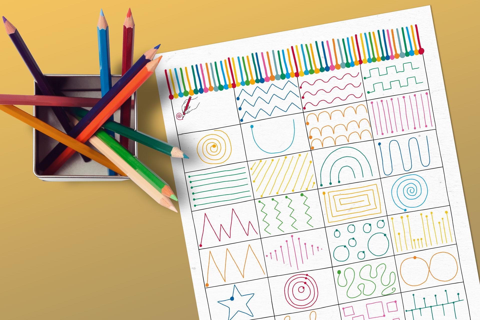 Becher mit Farbstiften neben einem Schreibübungsblatt mit Linien