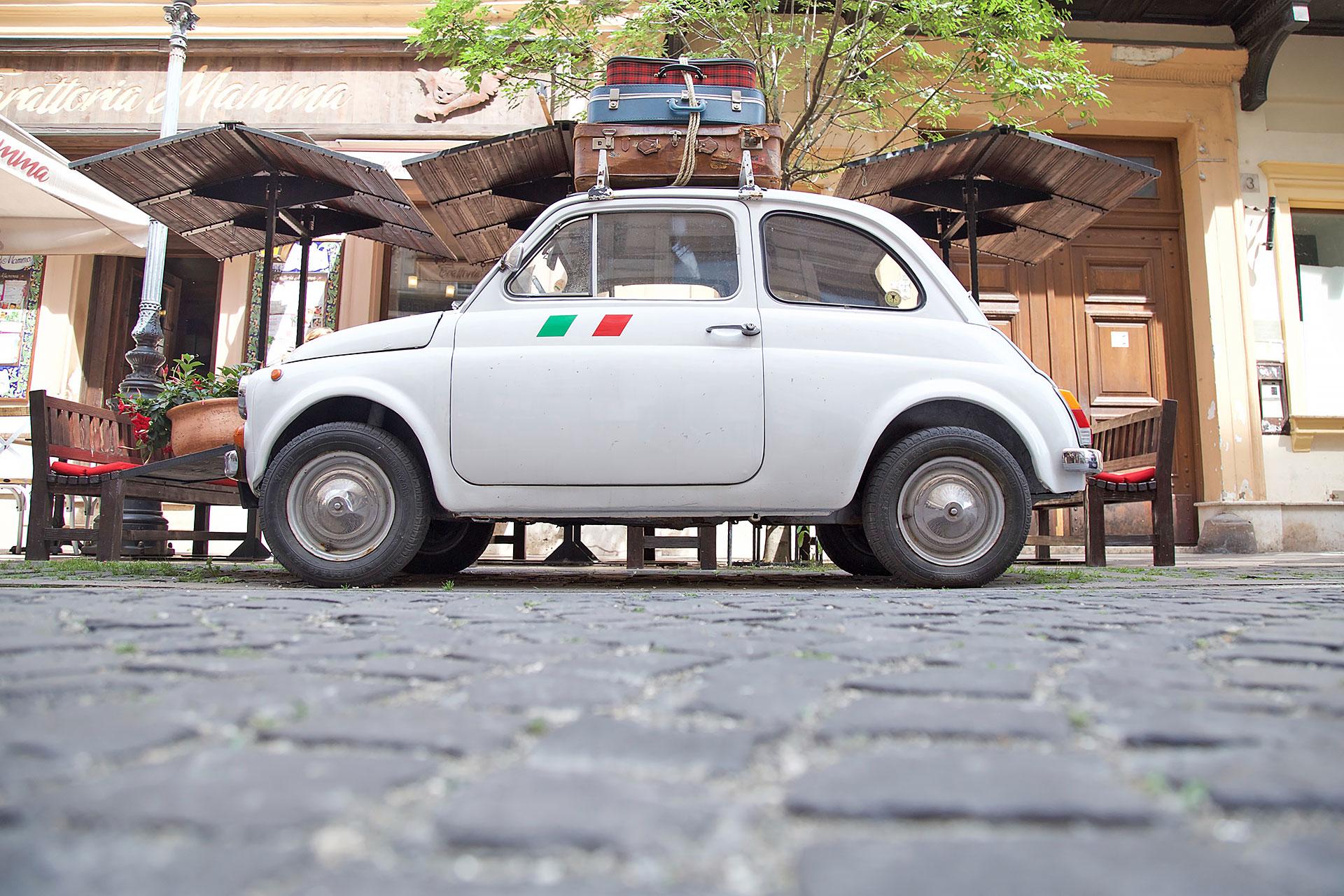 weisser Fiat 500 mit Koffern auf dem Autodach vor einem Restaurant