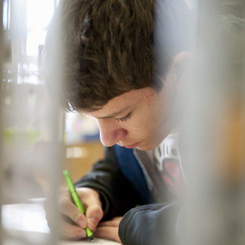 ein Schüler schreibt auf ein Aufgabenblatt